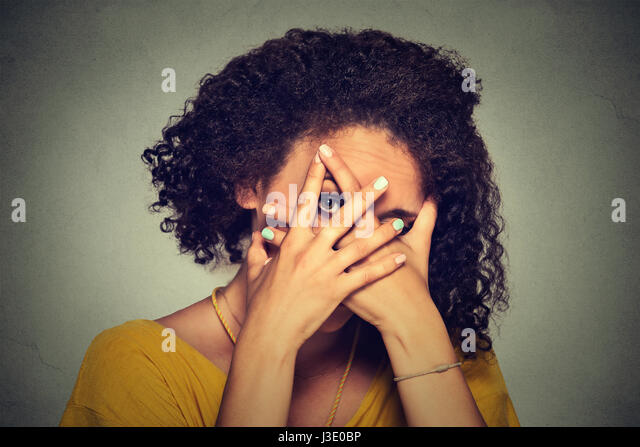 Closeup shy woman hiding face timid. Cute young caucasian woman peeking though hands. Gray background. - Stock Image