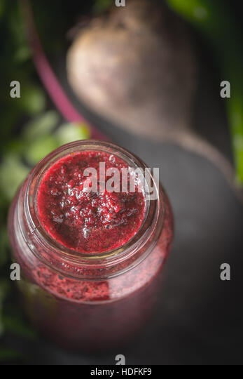 Vegetable smoothie with blurred ingredients on the dark stone background - Stock Image