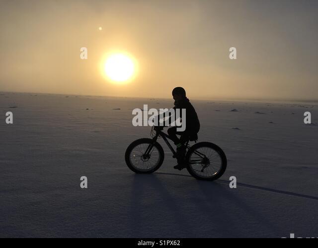 Fat tire biking down along the coast in Anchorage, Alaska at sunset. - Stock Image
