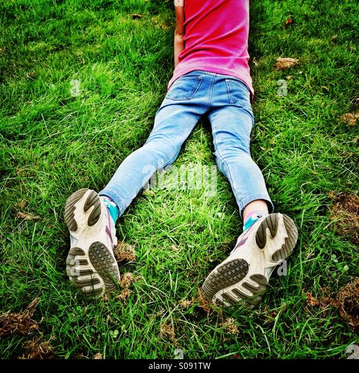 Legs of young girl lying in grass with soles of trainers facing upwards - Stock-Bilder