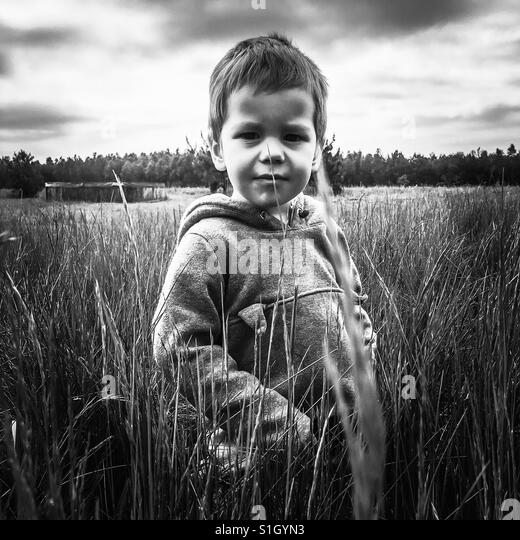 Small boy standing in the tall grass outside looking at the camera - Stock-Bilder