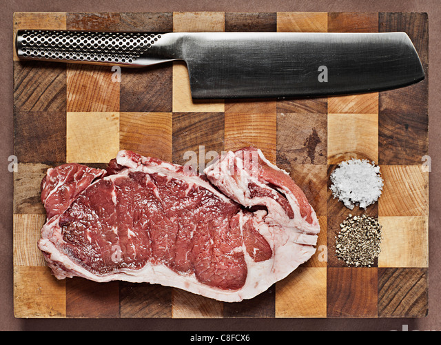 Sirloin Steak on Chopping Board with Knife - Stock Image