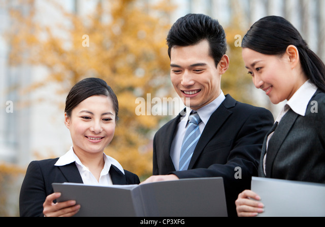 A team of businesspeople outside office buildings looking at a document - Stock Image