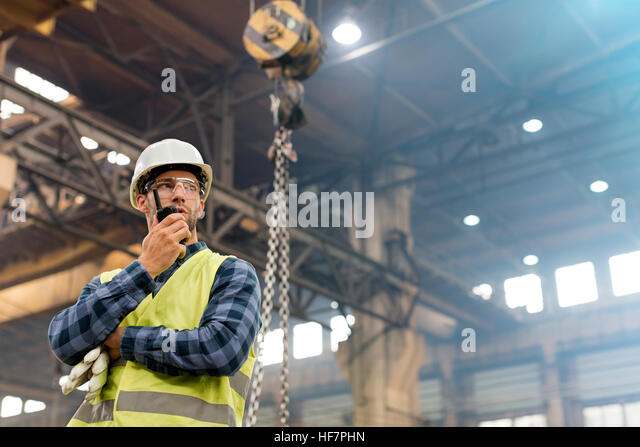 Steel worker with walkie-talkie in factory - Stock Image