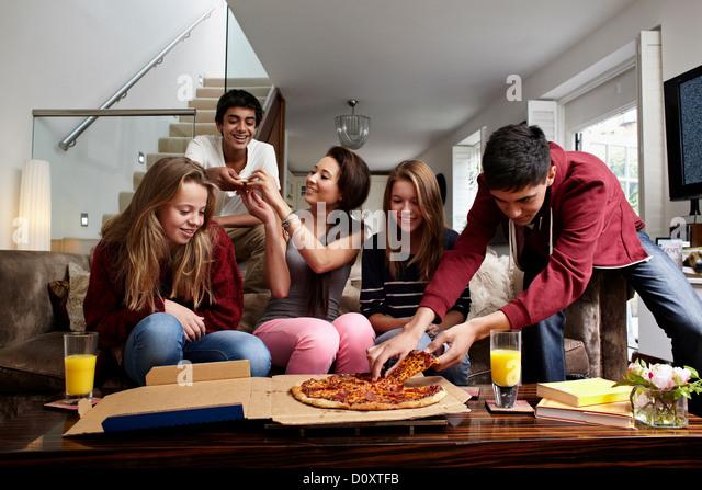 Teenagers having take away pizza - Stock Image