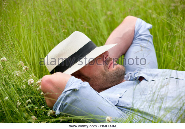 Serene man wearing fedora sleeping in tall summer grass - Stock-Bilder