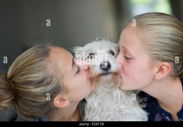 Two sisters posing with her dog for a picture - Stock Image