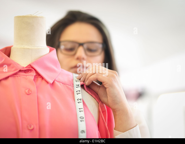 Fashion designer measuring garment in fashion design studio, close up - Stock Image