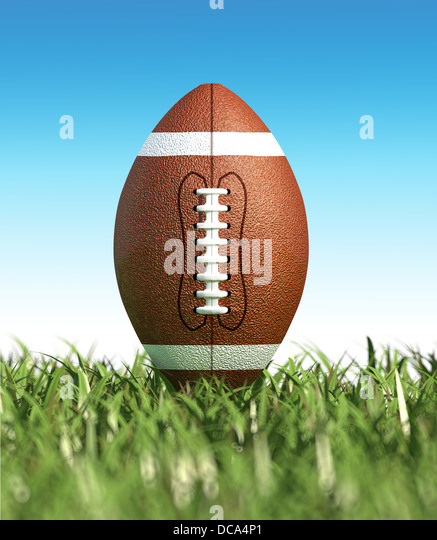 American football ball, on the grass, with blue sky in the background, no clouds. Side view, from ground level. - Stock Image