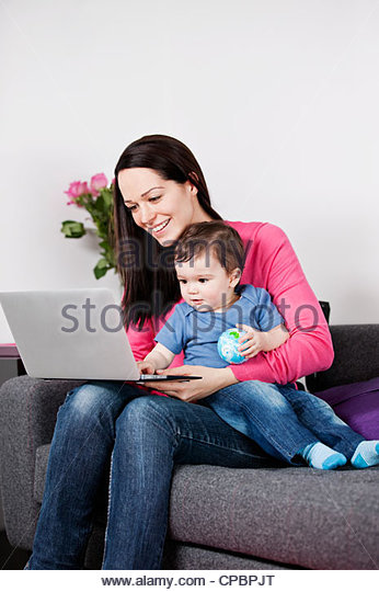 A mother and her baby son sitting on a sofa looking at a laptop, baby holding a globe ball - Stock-Bilder