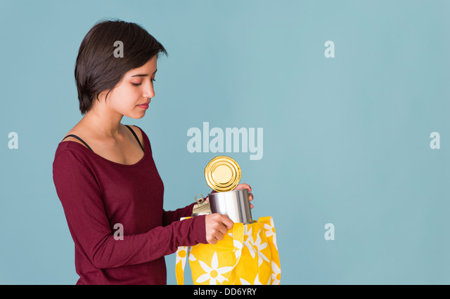 Portrait of young multiracial woman recycling metal cans - Stock Image