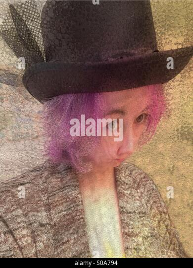 Strange Woman Wearing a Black Hat - Stock Image