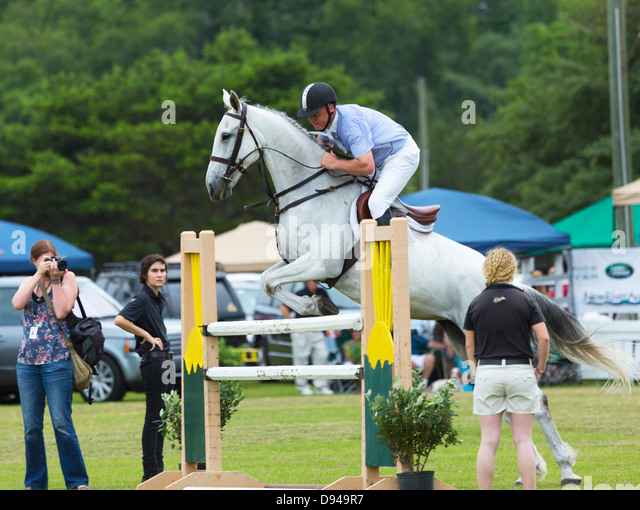 A horse and rider jump a vertical fence in a six-bar show jumping competition - Stock Image