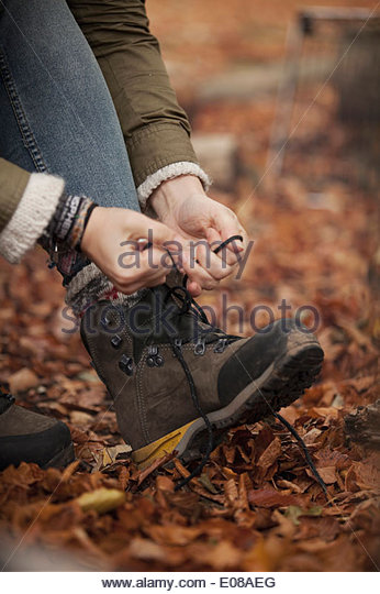 Cropped image of woman tying shoelace in forest - Stock Image