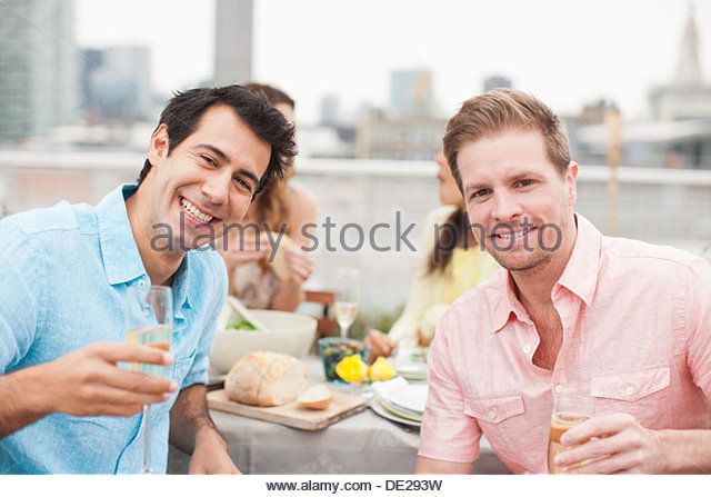 Laughing friends drinking Champagne at outdoor party - Stock Image