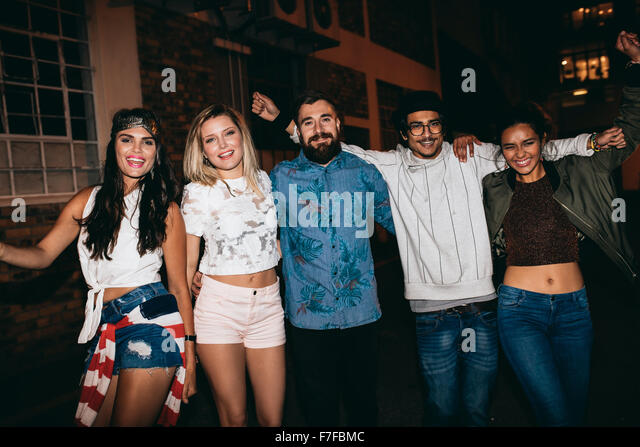 Portrait of cheerful young people in a rooftop party at night. Young men and women celebrating success outdoors. - Stock Image