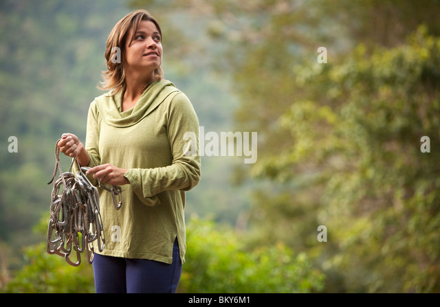 A woman prepares her rope for a climb in Brazil. - Stock Image