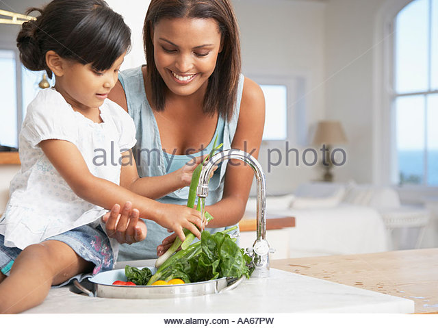 Mother and daughter preparing a meal in kitchen - Stock-Bilder