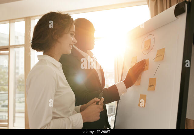 Two business colleagues working on project together. Business people putting their ideas on whiteboard during a - Stock Image