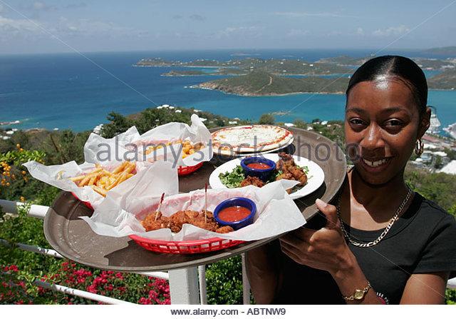St. Thomas USVI Paradise Point Black female waitress conch fritters Charlotte Amalie Harbor Caribbean Sea - Stock Image