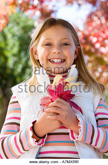 Girl 7 9 standing in autumn garden holding red maple leaf smiling close up portrait - Stock Image