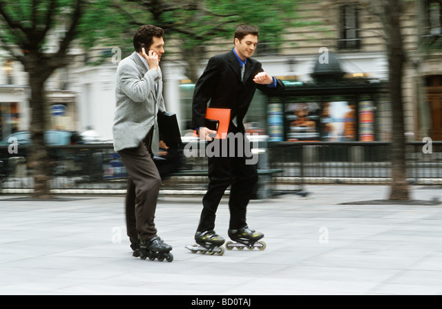 Men in business attire rollerskating together along sidewalk, one phoning, the other looking at watch - Stock-Bilder