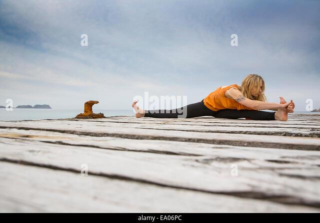 Mid adult woman practicing yoga on wooden sea pier - Stock-Bilder