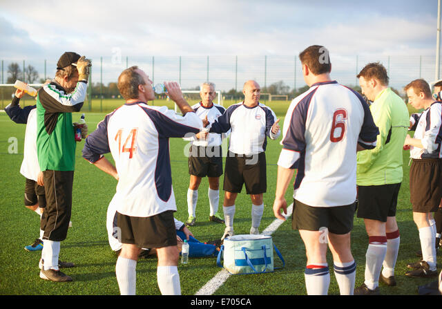 Football players resting and hydrating at half time - Stock Image