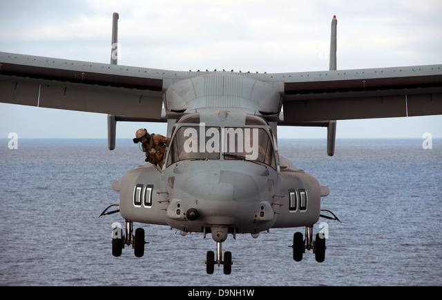 A US Marine Corps MV-22 Osprey tiltrotor aircraft approaches to land on the flight deck of the amphibious transport - Stock Image