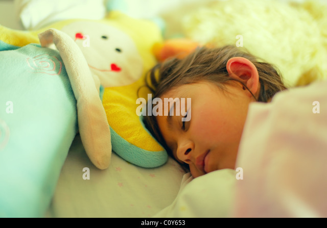 Girl has lie in with toy doll in bed. - Stock Image