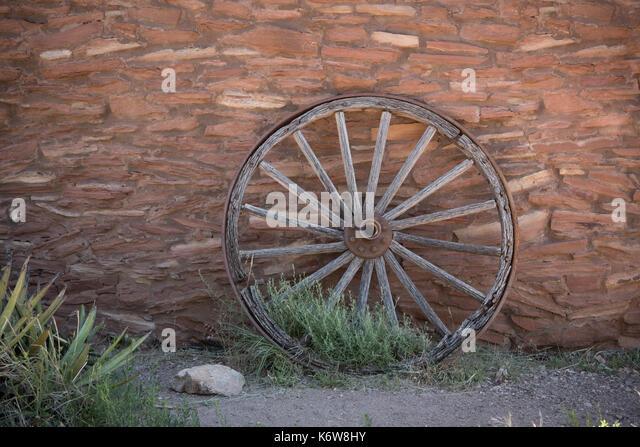Wooden Wheel on Brick Wall Horizontal Image - Stock Image