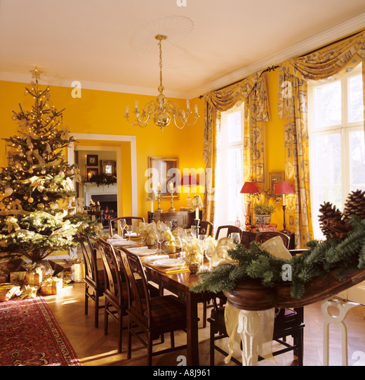 Christmas dinner table set with tree - Stock Image