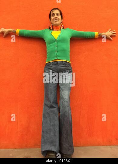 Woman with flared jeans and green cardigan and orange background - Stock Image