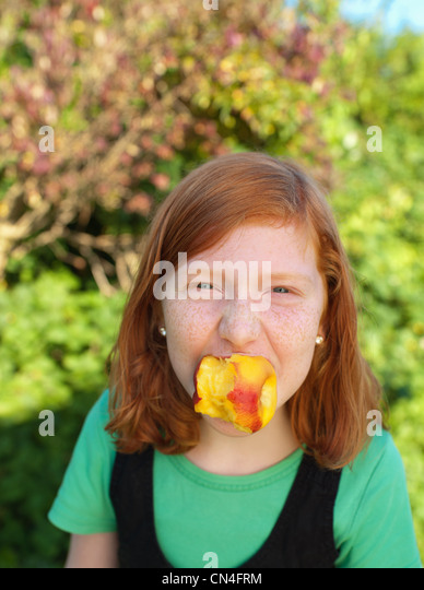 Young girl holding peach in mouth, portrait - Stock Image