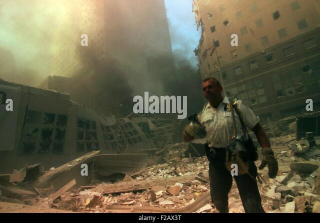 New York City policeman in ruins following September 11th terrorist attack on World Trade Center. He stands in the - Stock-Bilder