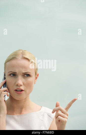 Woman making angry face while talking on cell phone - Stock Image