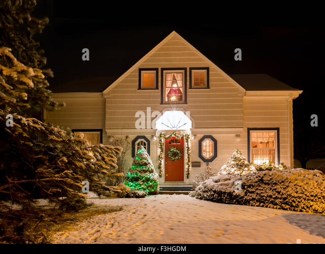 A house decorated with a wreath, garland and Christmas lights an a clear winter night. - Stock Image