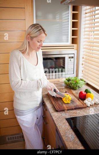 Side view of woman cutting bell pepper - Stock Image