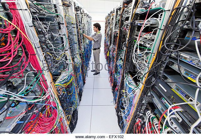 Technician checking cables in Server room of data center - Stock Image