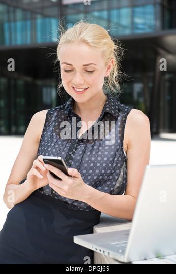 Businesswoman using smartphone - Stock-Bilder