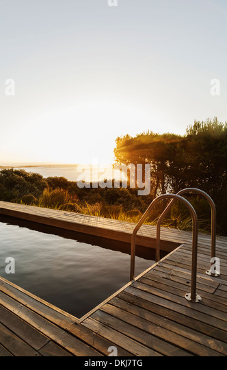 Sunset in background of lap pool - Stock Image