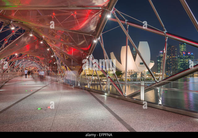 Double Helix Bridge and Art and Science Museum and downtown central financial district at night, Singapore, Southeast - Stock Image