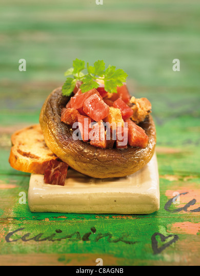 Mushroom tops filled with diced ham - Stock Image