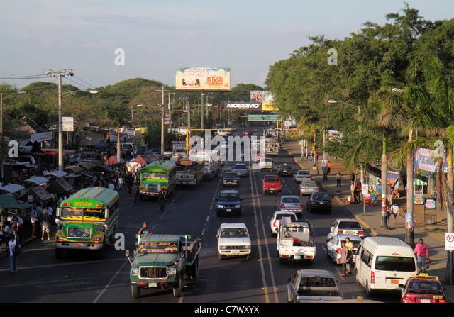 Nicaragua Managua Pista de la Resistencia street scene large avenue bus truck car traffic pedestrian tree lined - Stock Image