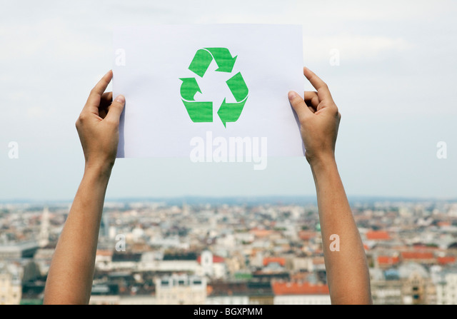 Arms holding paper green recycling sign - Stock Image