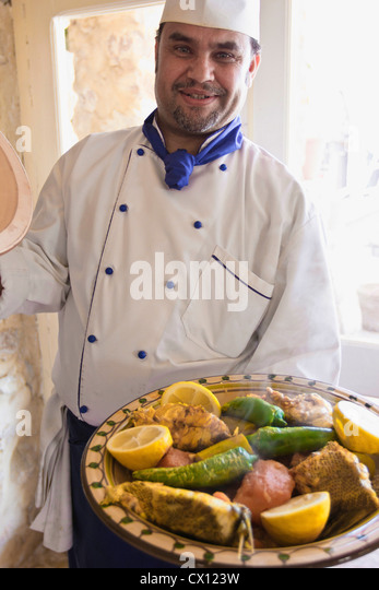 Chef with fish and vegetable dish in Djerba, Tunisia - Stock Image