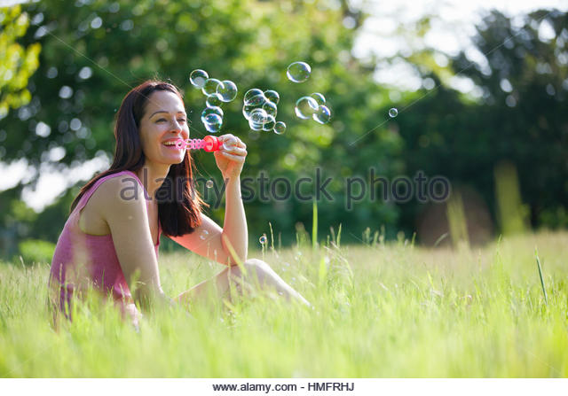 Happy woman blowing bubbles with bubble wand in sunny summer rural grass - Stock-Bilder