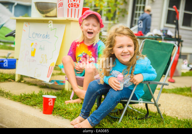 Candid portrait of two smiling girls selling lemonade and popcorn at yard sale - Stock Image