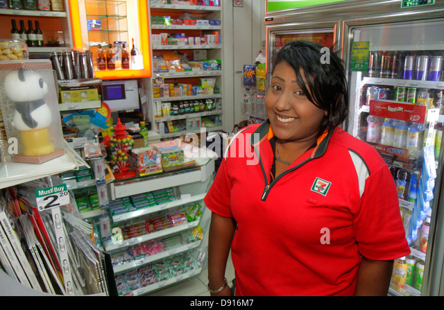 Singapore Kallang Road Asian woman 7-Eleven convenience store uniform employee manager job - Stock Image