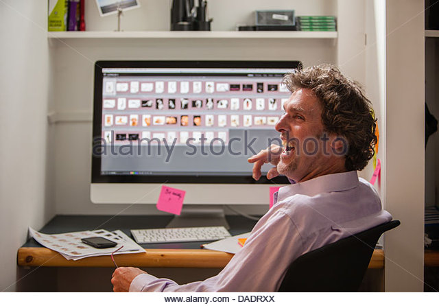 Portrait of mature male in front of computer screen - Stock Image